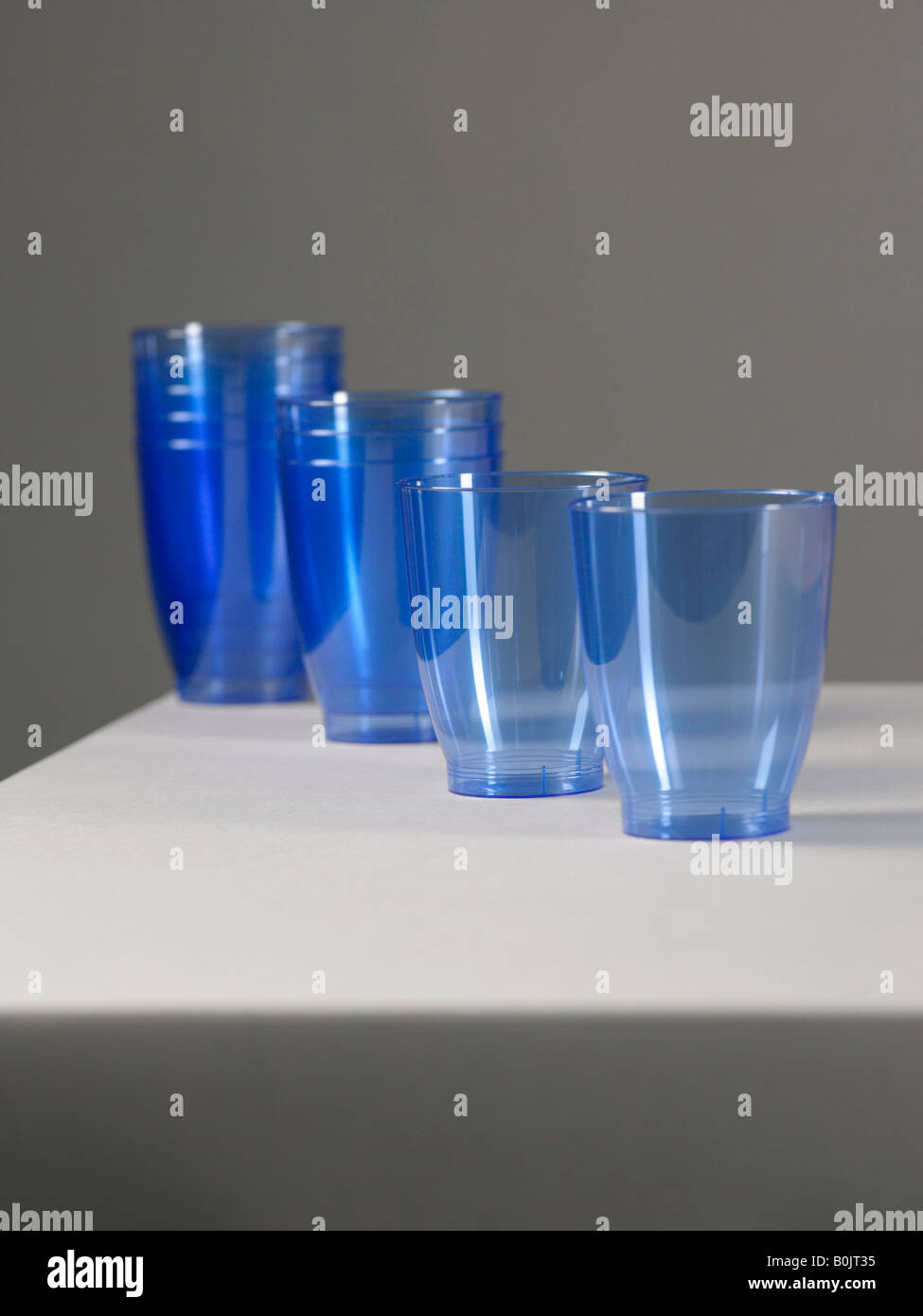 blue plastic cups on grey background - Stock Image