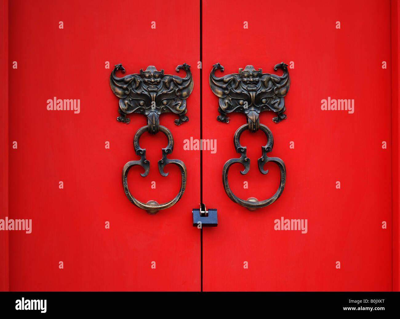 Bat knocker on red door in Beijing,China - Stock Image