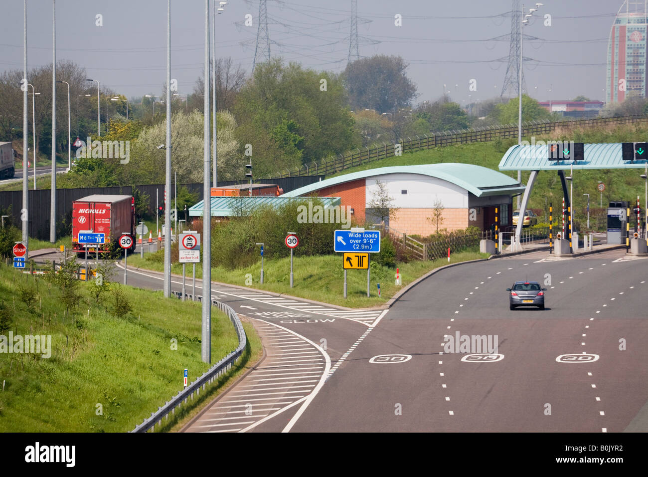 M6 TOLL MOTORWAY from above with vehicle approaching toll booths and lorry in wide load lane West Midlands England - Stock Image