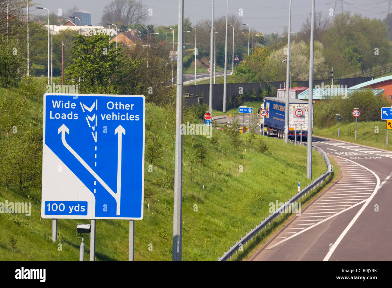 M6 TOLL MOTORWAY from above with sign and lorry in wide load lane.  West Midlands England UK - Stock Image