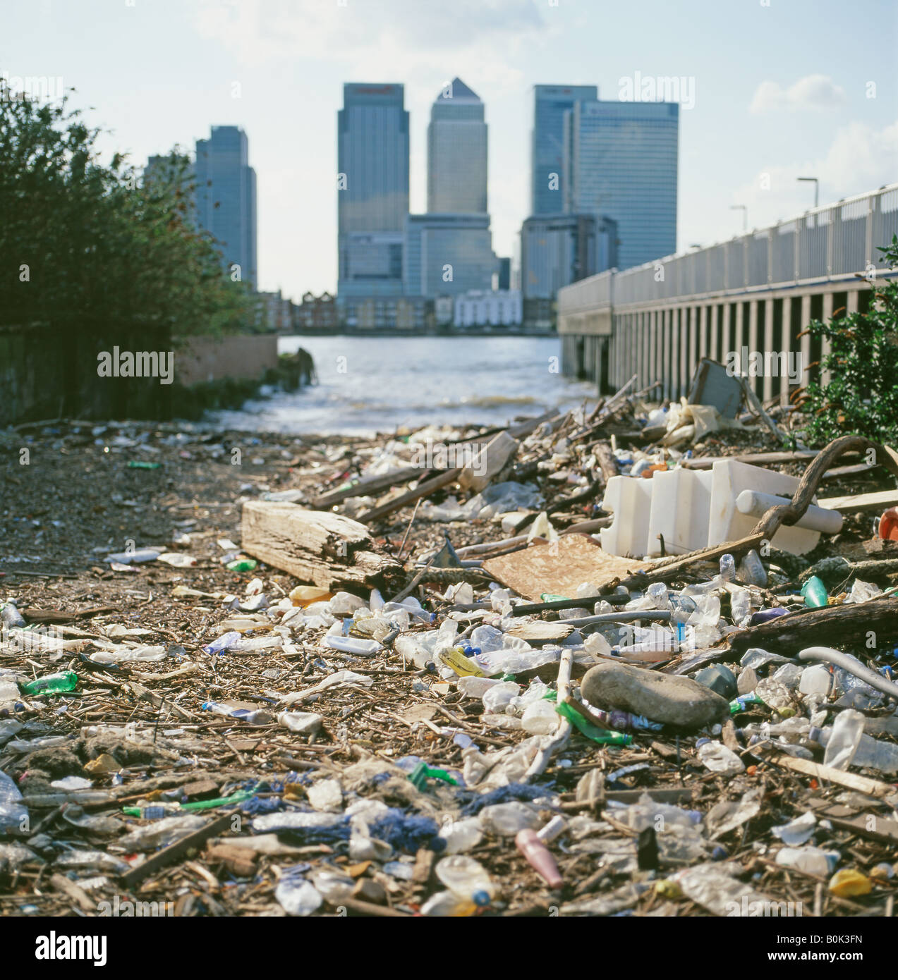 Environmental plastic pollution on the Greenwich side of the River Thames with view of Canary Wharf, banks & - Stock Image