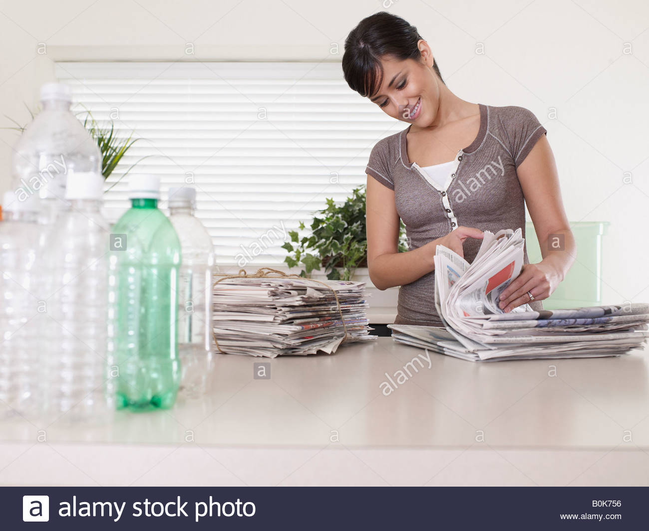 Woman in kitchen with recyclable materials smiling - Stock Image
