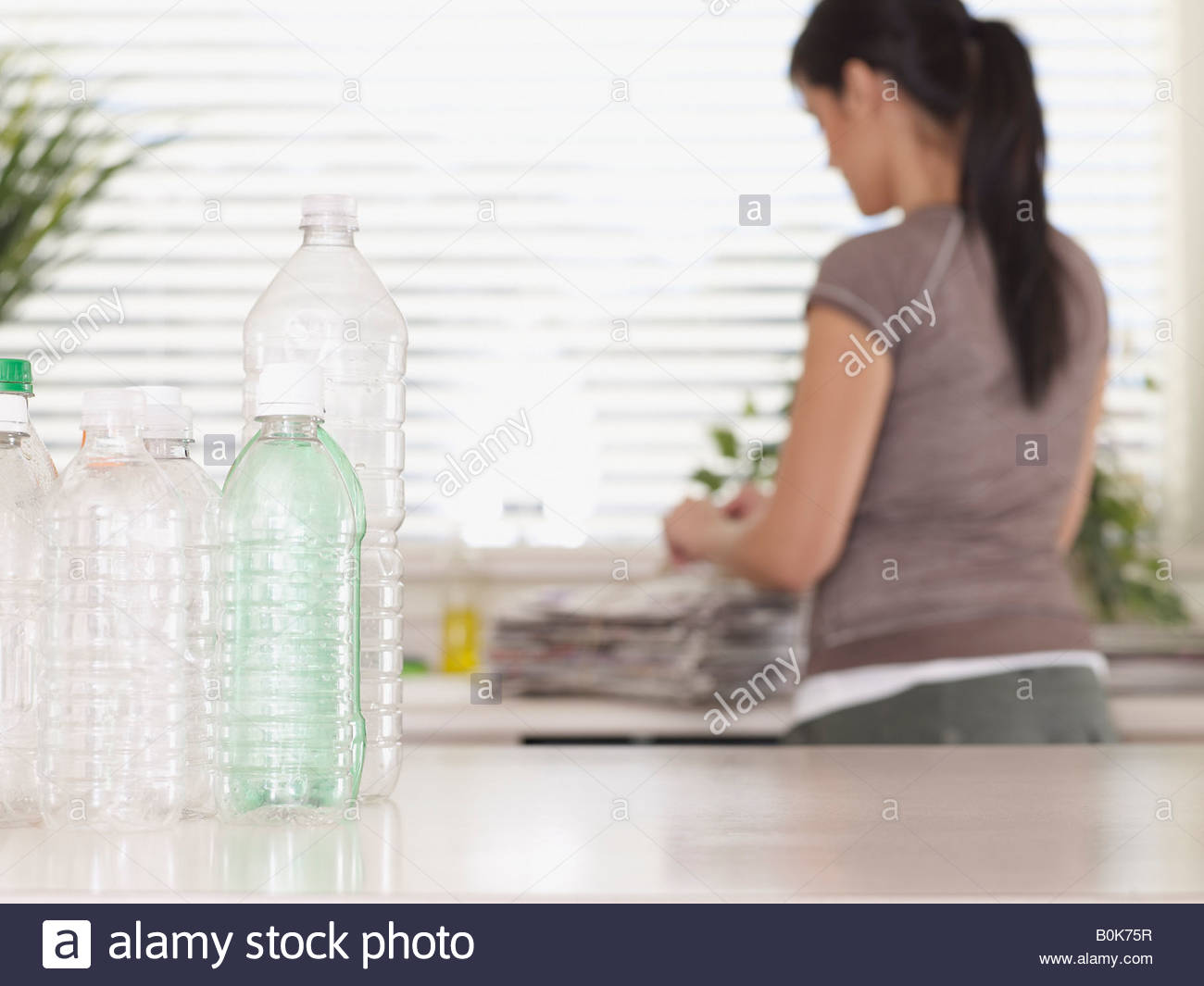 Woman in kitchen with recyclable materials - Stock Image