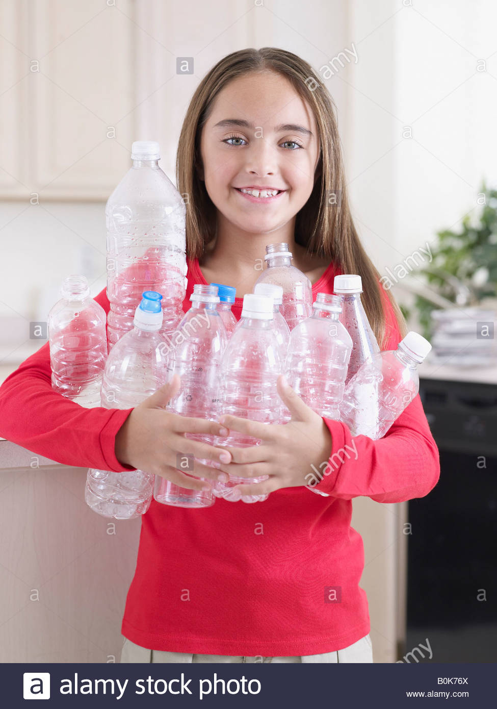 Young girl in kitchen with recyclable plastic bottles smiling - Stock Image