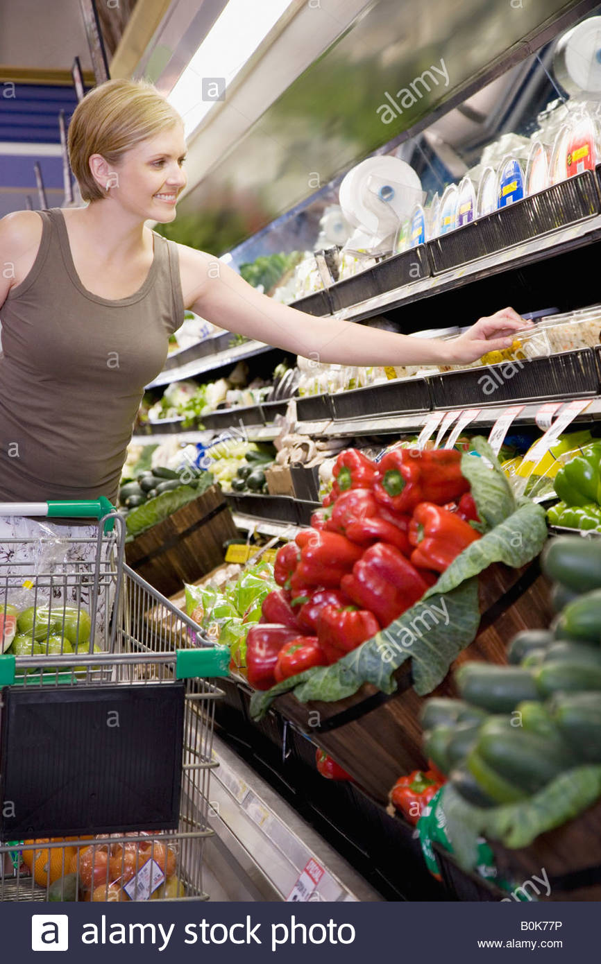 Woman in grocery store produce aisle smiling - Stock Image