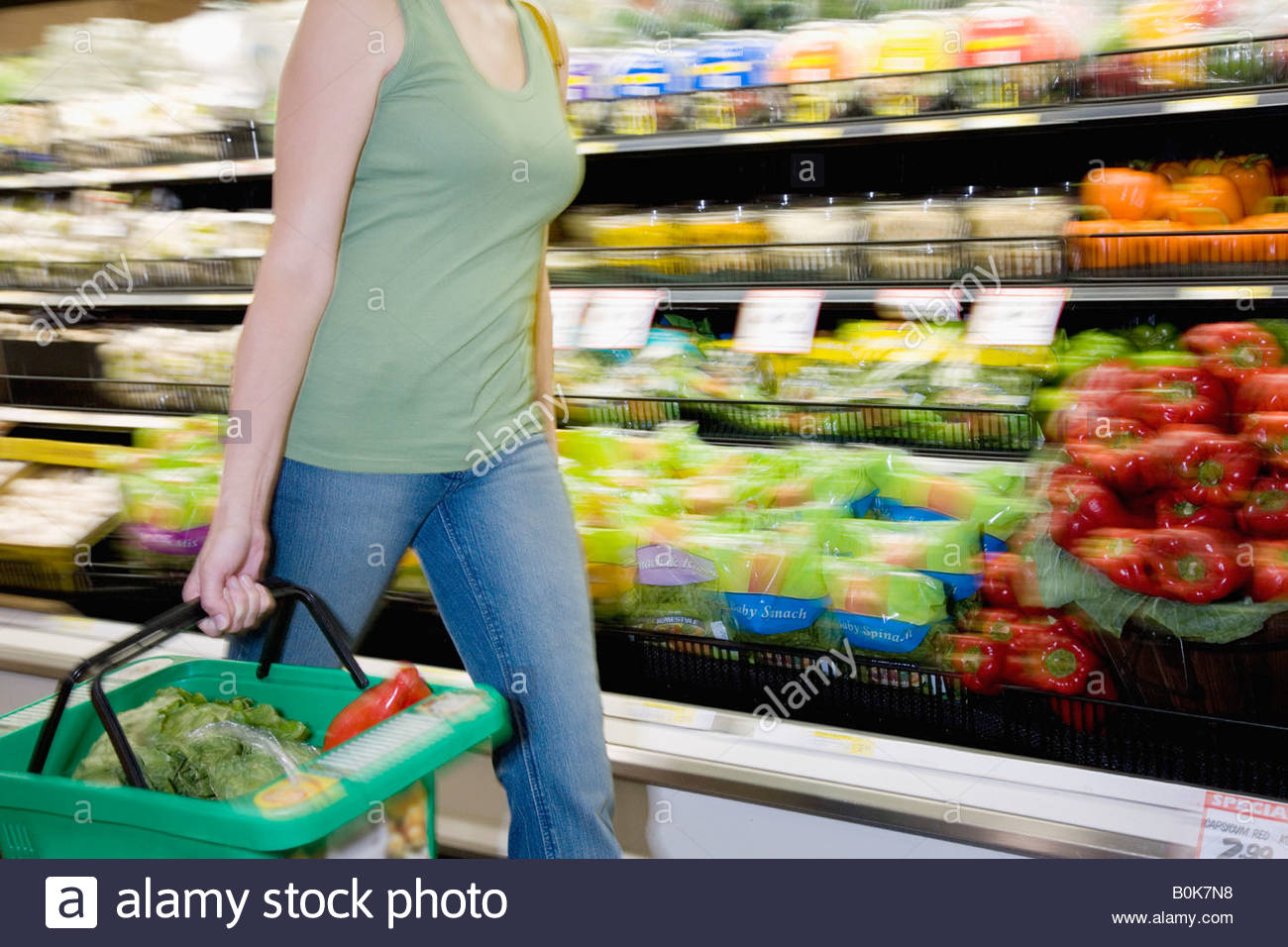 Woman in grocery store produce aisle with shopping basket - Stock Image