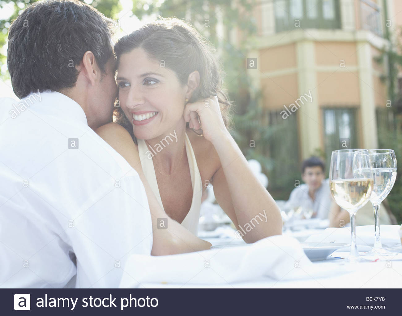Couple at outdoor party whispering and smiling - Stock Image