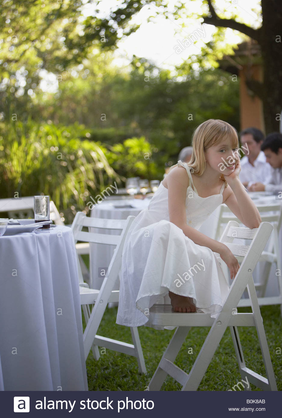 Young girl crouched on chair at outdoor party smiling Stock Photo