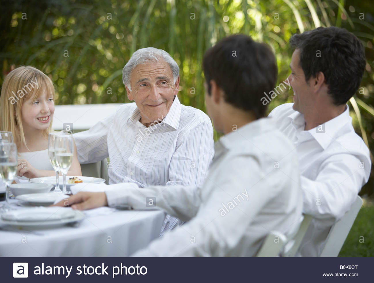 Senior man and young girl at outdoor party talking to two men and smiling - Stock Image