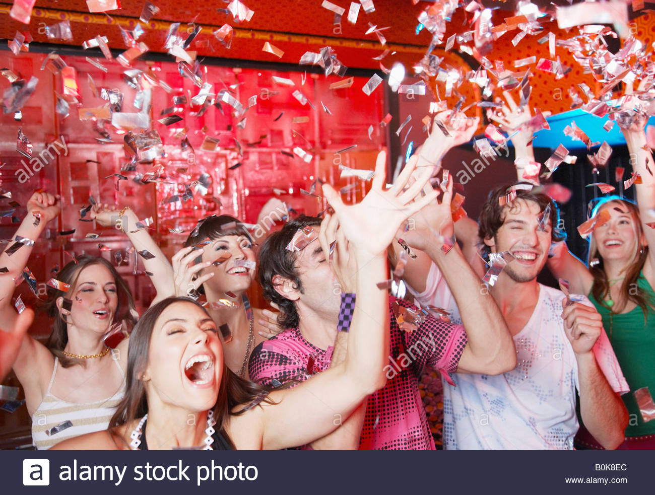 group of people in a nightclub partying and throwing confetti - Stock Image