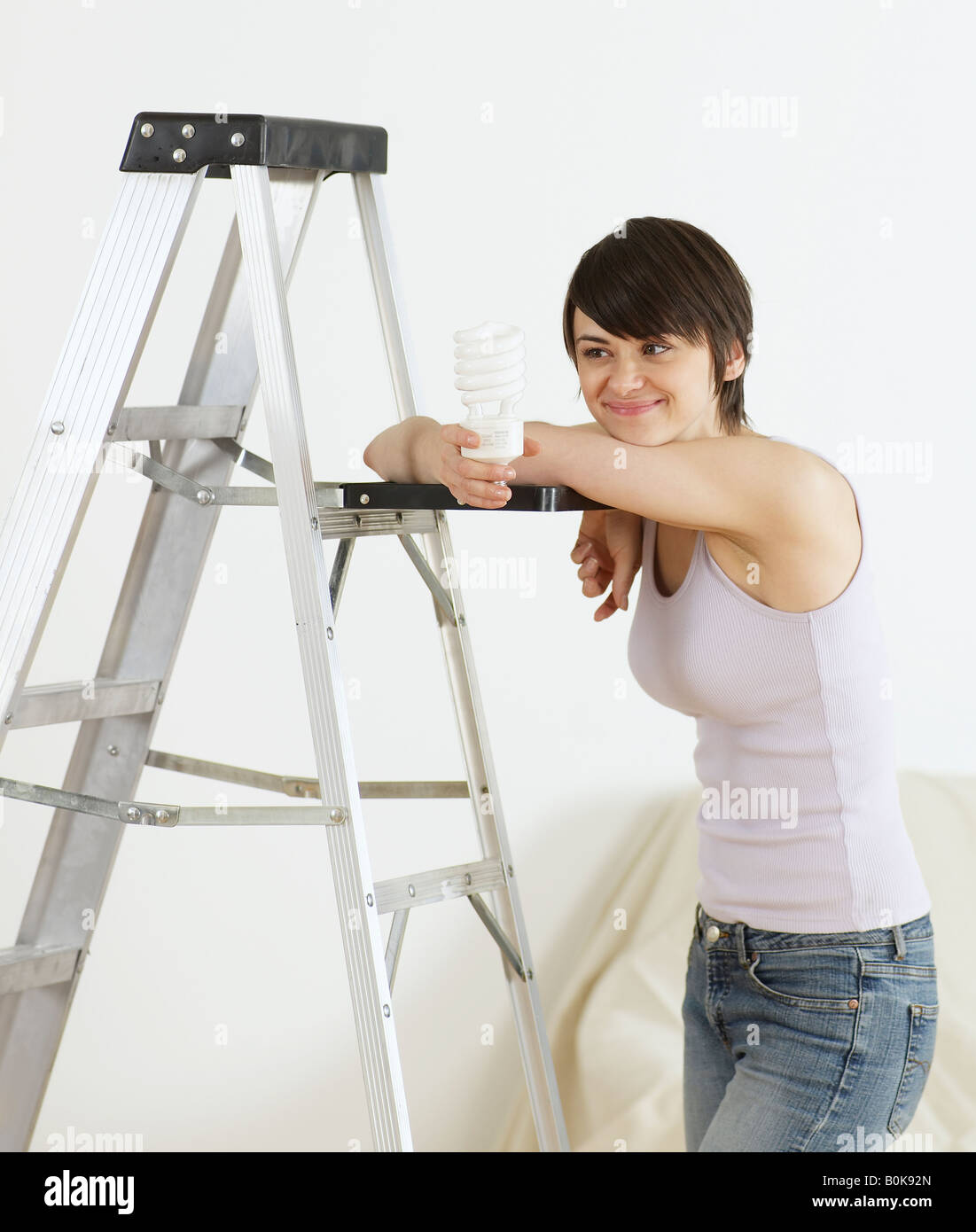 Young Woman Leaning on Stepladder and Holding Light bulb Stock Photo