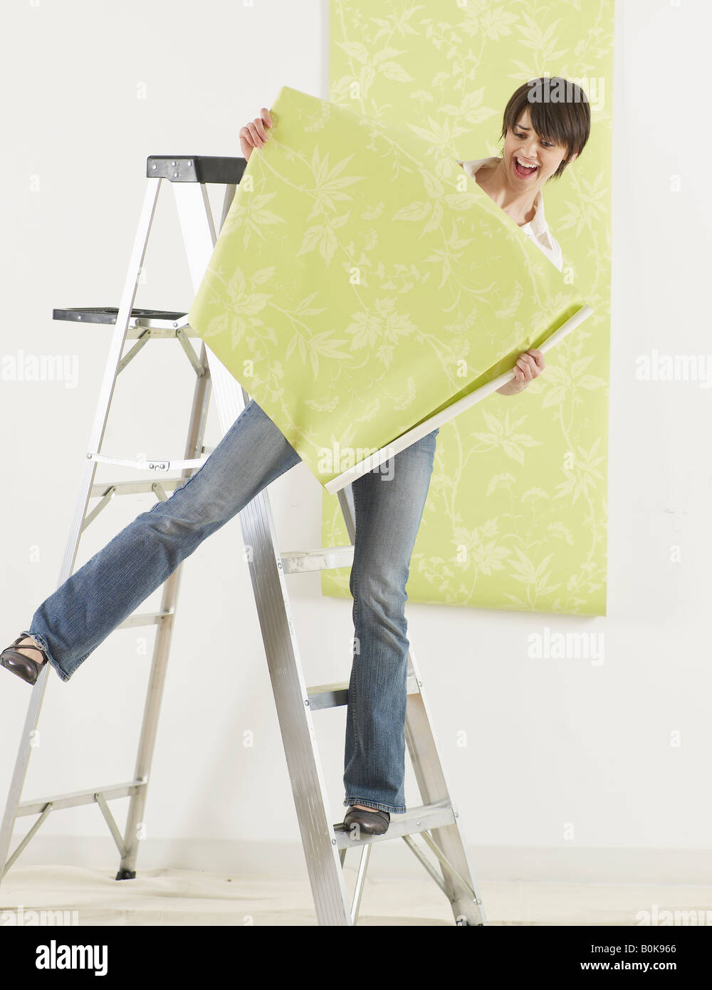 Young Woman Balancing on Stepladder and Holding Wallpaper Stock Photo