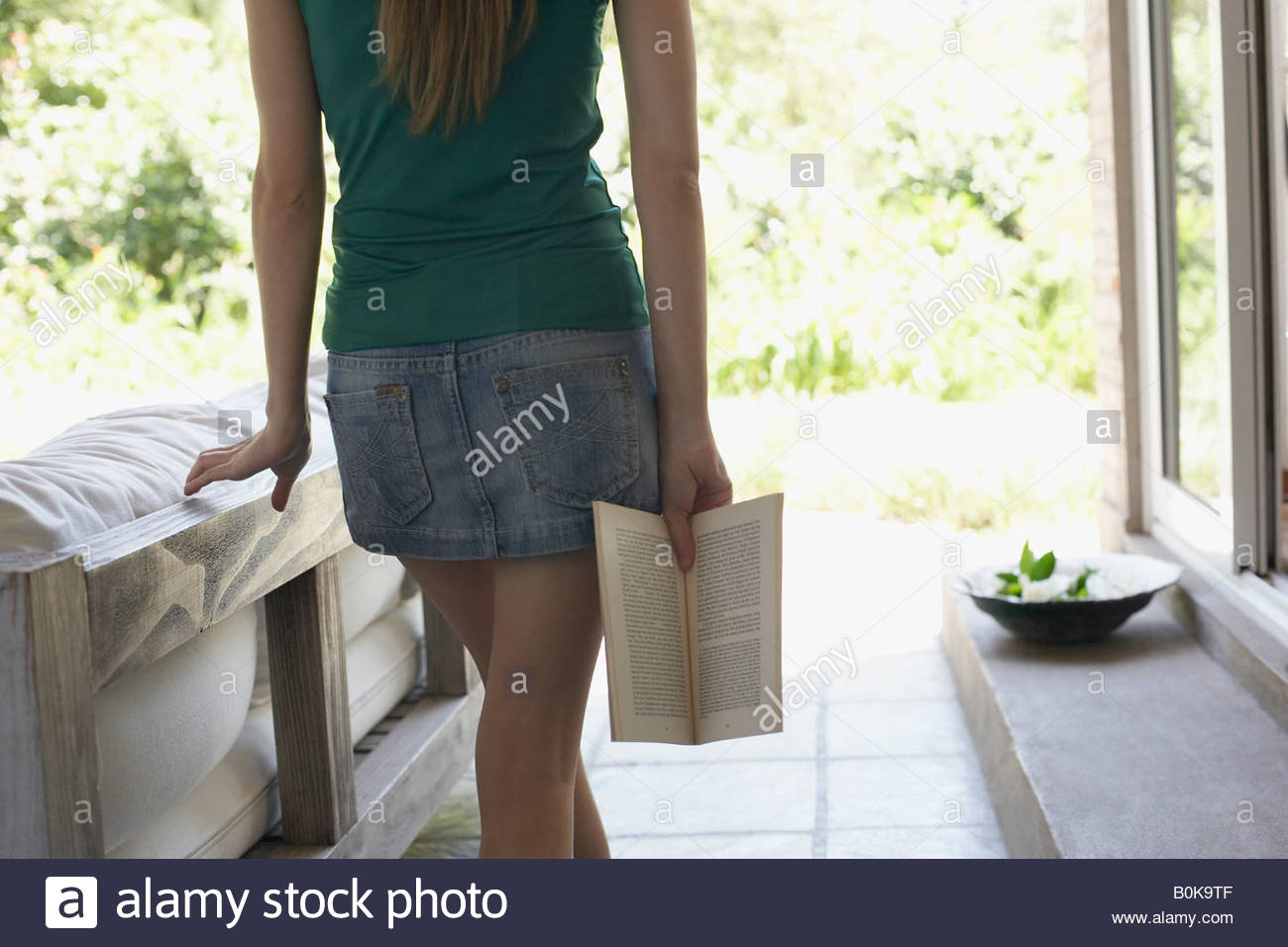 Woman standing outdoors on patio with a book - Stock Image