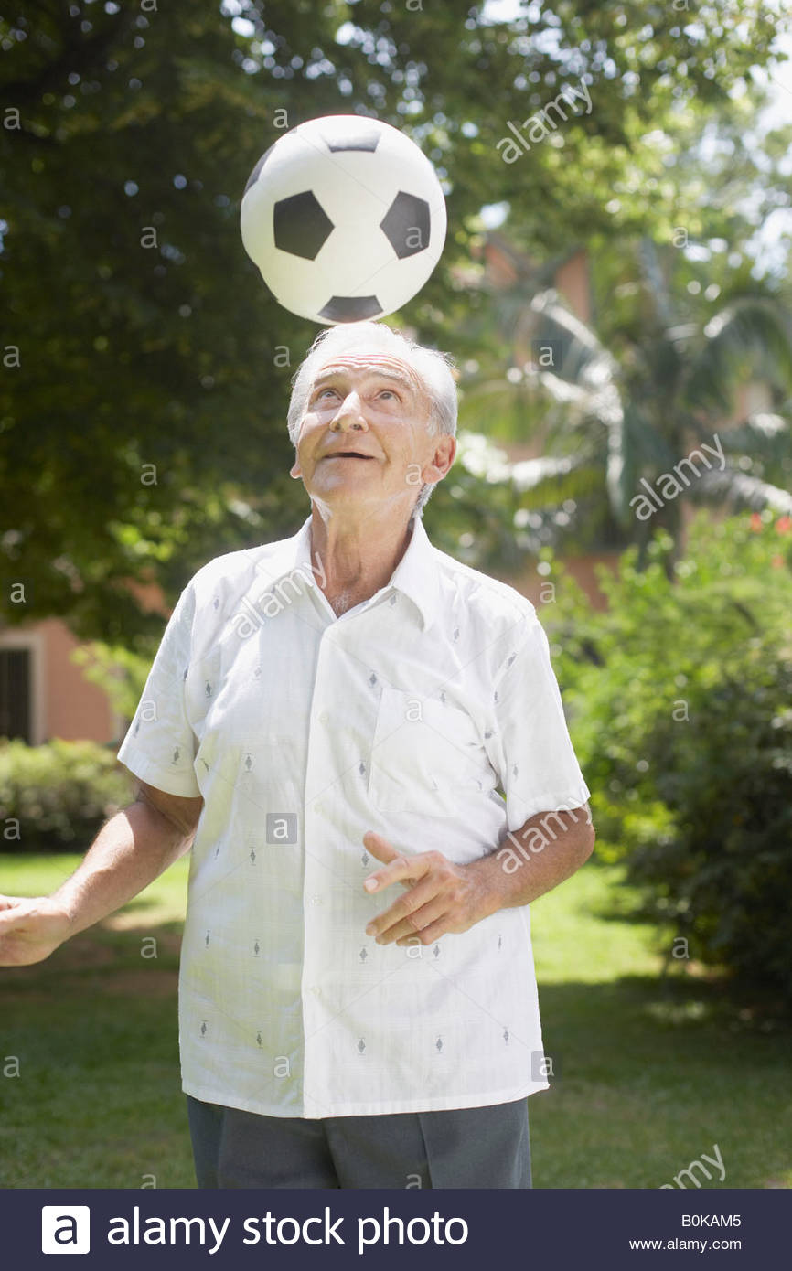 Senior man outdoors balancing soccer ball on head - Stock Image