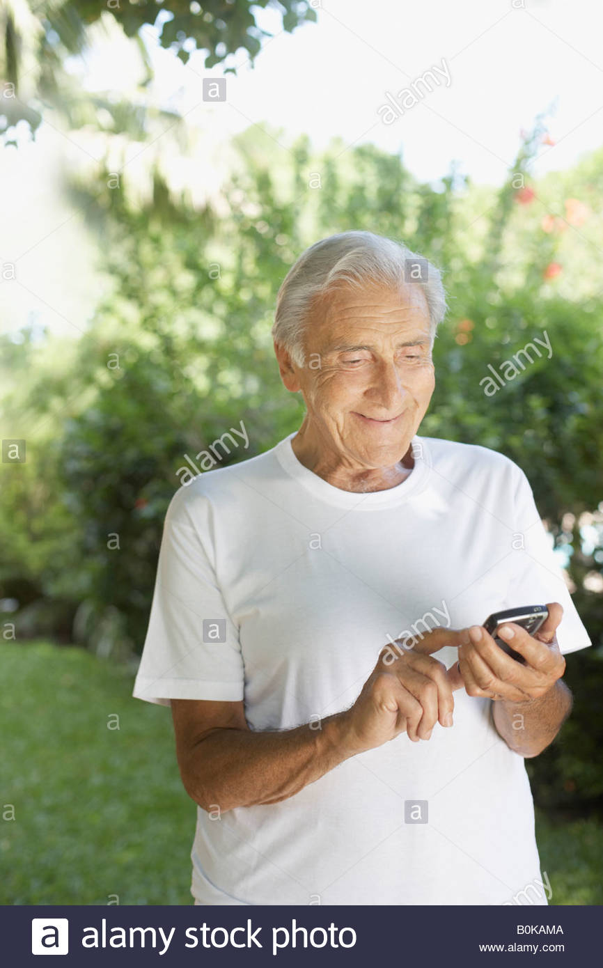 Senior man outdoors using a personal digital assistant and smiling - Stock Image
