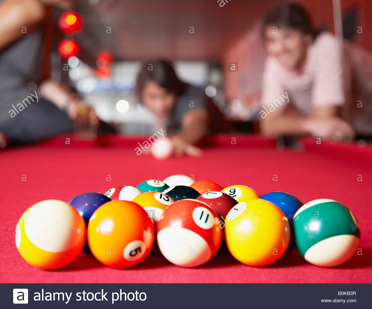 three people playing pool focussing on pool balls - Stock Image