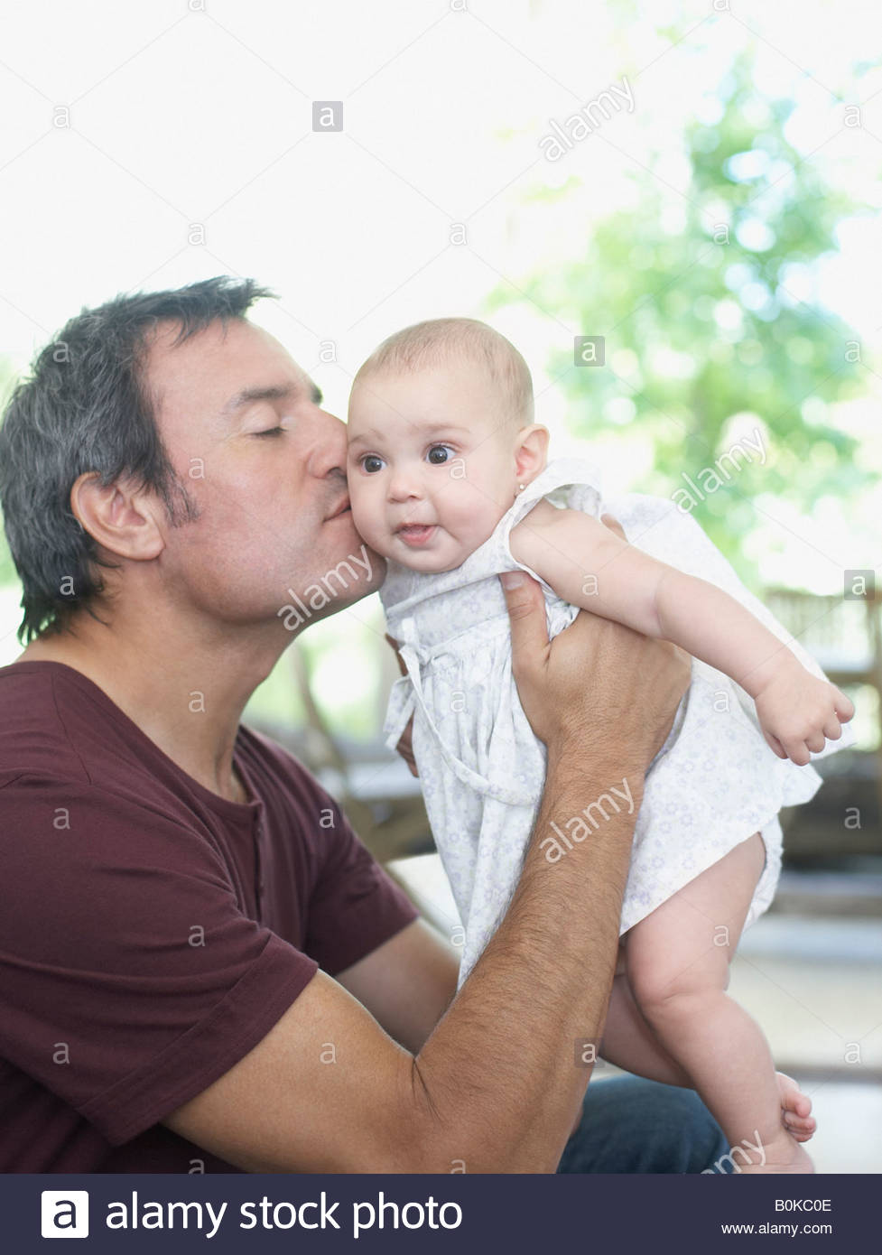 Man sitting outdoors kissing baby - Stock Image