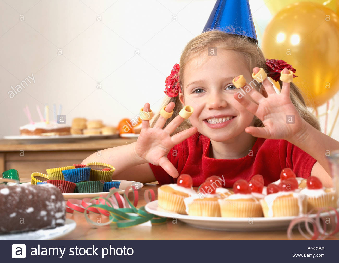 Young girl at birthday party playing with food and smiling - Stock Image