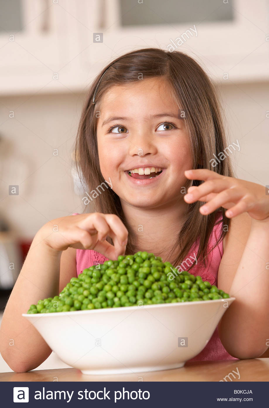 Young girl in kitchen with a bowl of green peas smiling - Stock Image