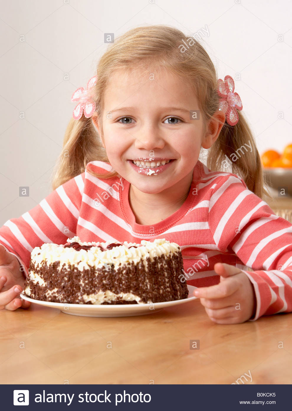 Young girl in kitchen eating cake and making a mess smiling - Stock Image