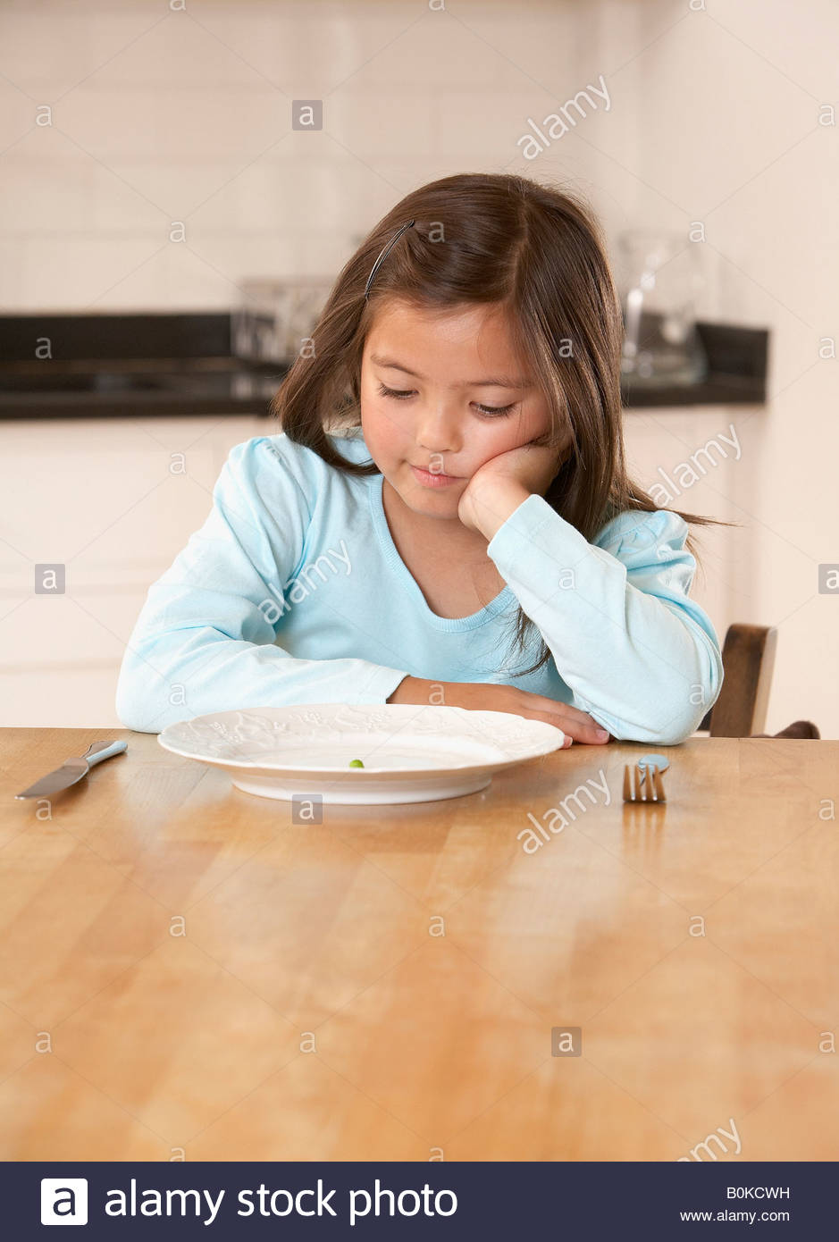 Young girl in kitchen with a single green pea on her plate looking unhappy - Stock Image