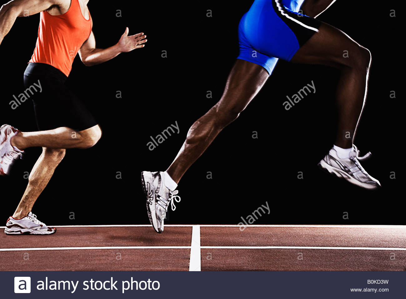 Two runners on race track with one jumping up in air - Stock Image