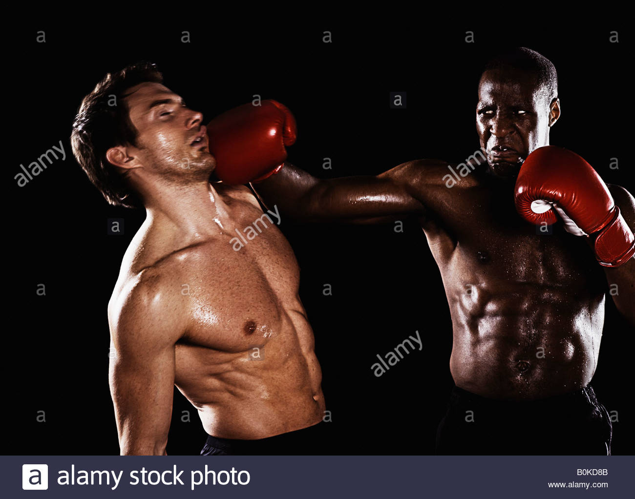 Two men boxing with one being hit - Stock Image