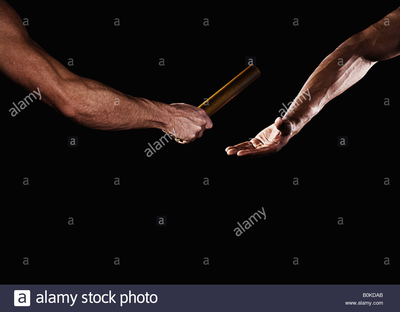 Two relay runners handing off a baton - Stock Image