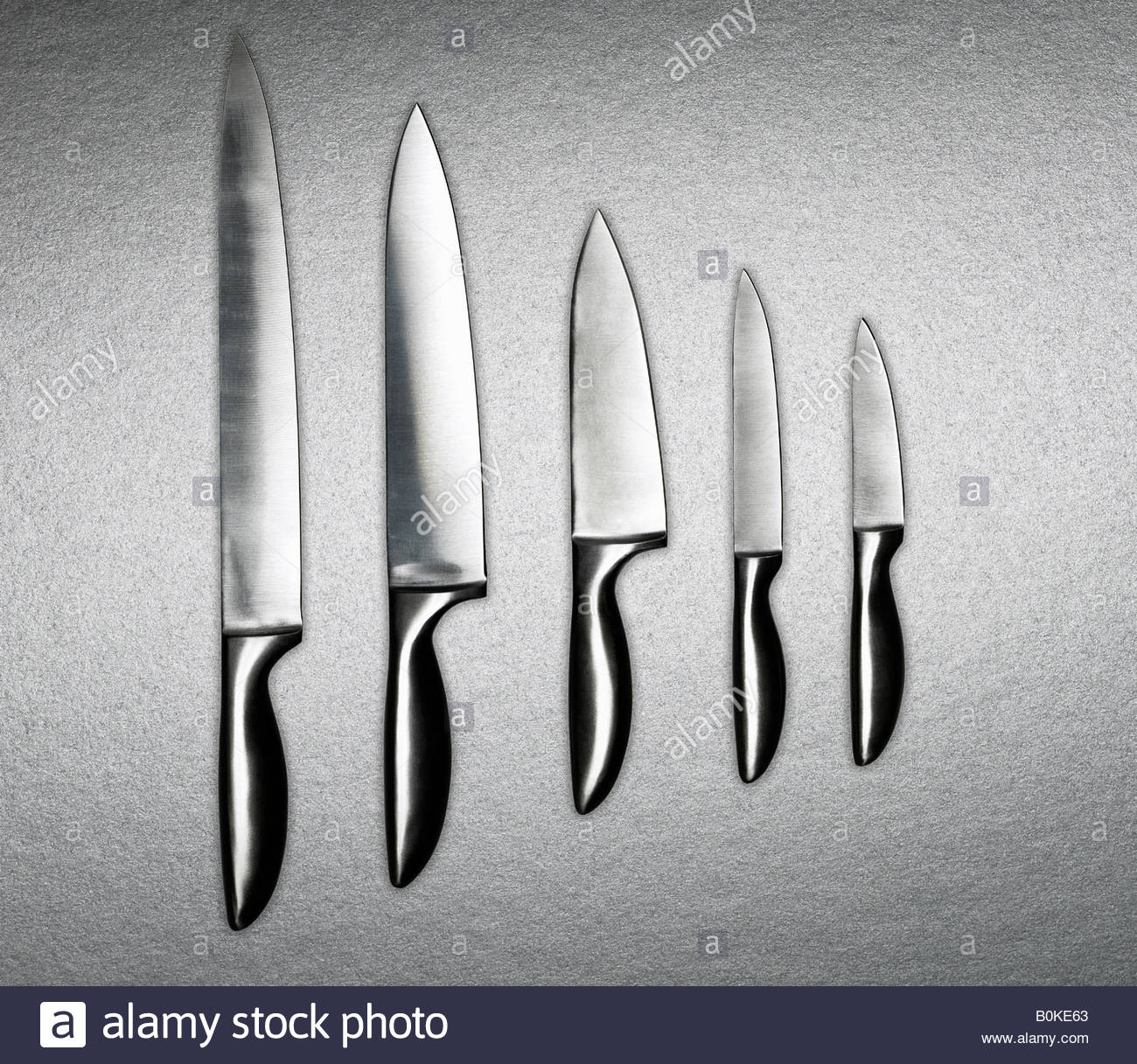 A variation of silver knives in a row - Stock Image