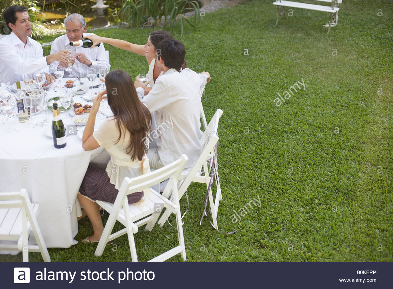 five people at outdoor party socially drinking - Stock Image