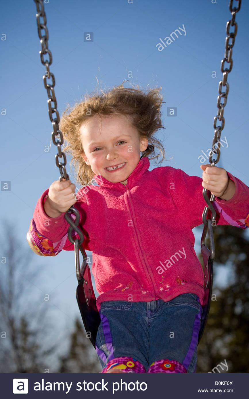7 year old girl swinging at playground. - Stock Image