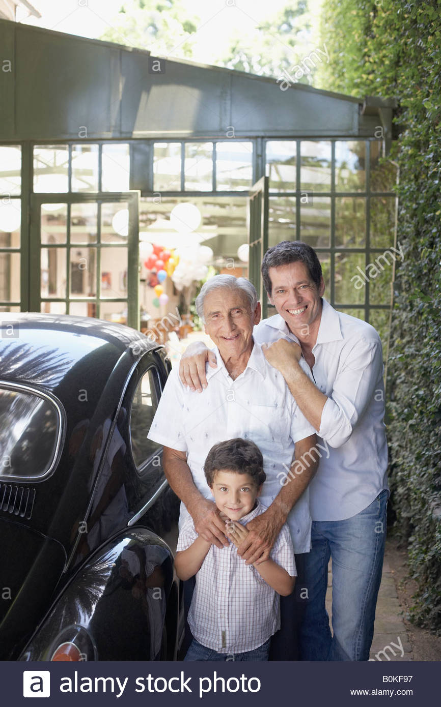 Senior man with man and young boy outdoors standing beside car smiling - Stock Image