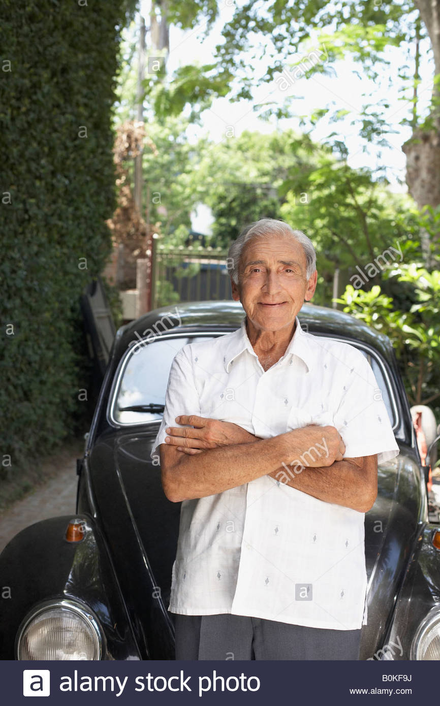 Senior man standing outdoors by car smiling - Stock Image