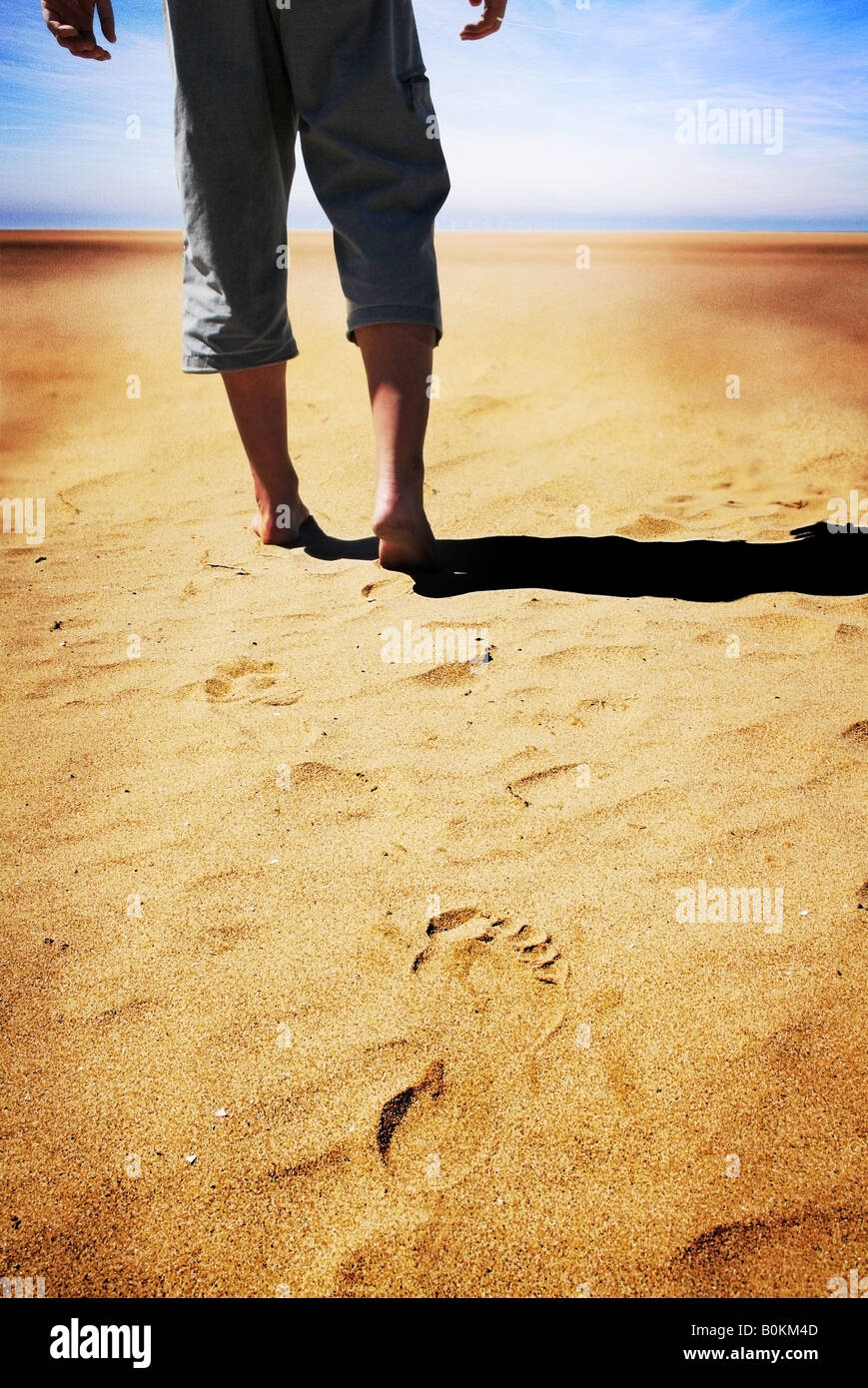 man walking bare foot alone on sand with clear footprint left in soft sand - Stock Image