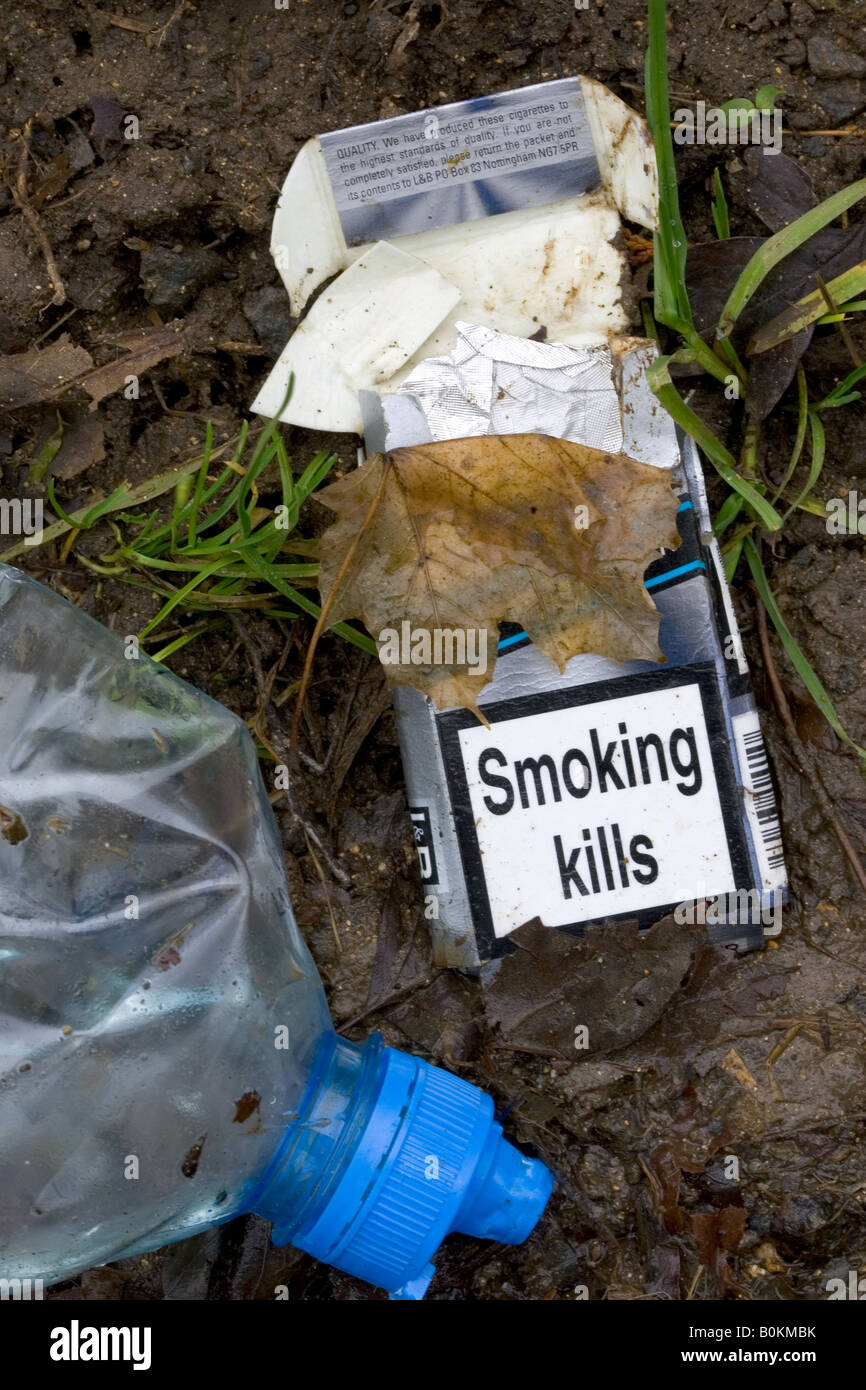 Cigarette packet showing SMOKING KILLS and plastic bottle discarded by road Oxfordshire UK - Stock Image