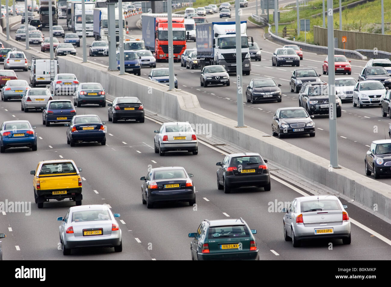 Traffic congestion of cars and lorries travelling in both directions on M25 motorway London United Kingdom - Stock Image