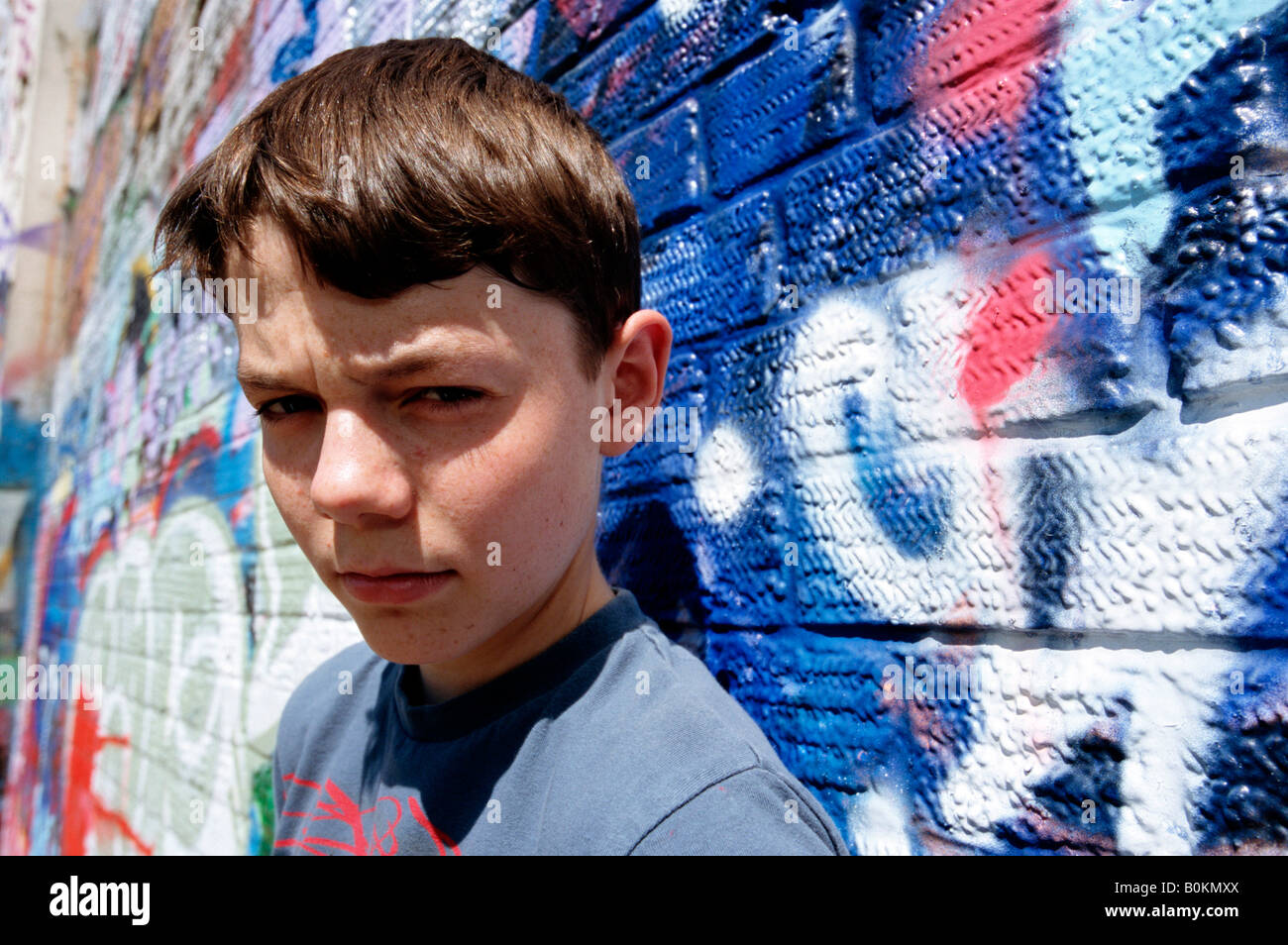 Teenaged boy in front of graffitti wall - Stock Image