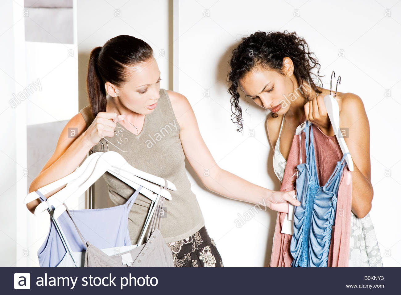 Two friends outside the changing room of a shop, waiting to try on clothes - Stock Image
