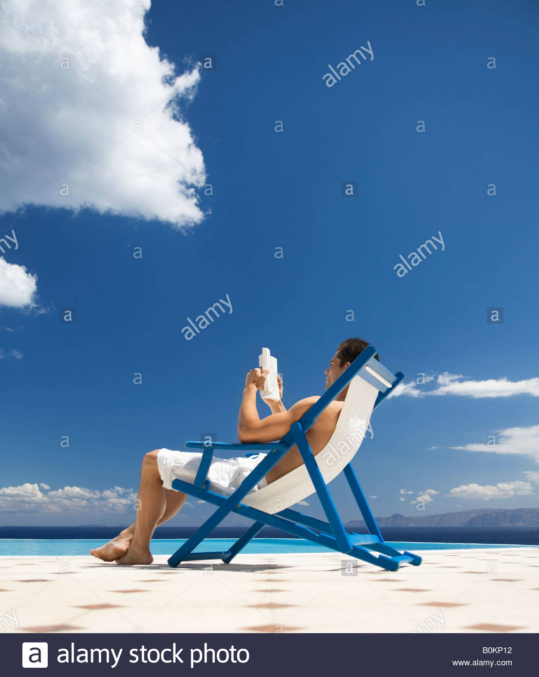 A man relaxing in a deck chair - Stock Image