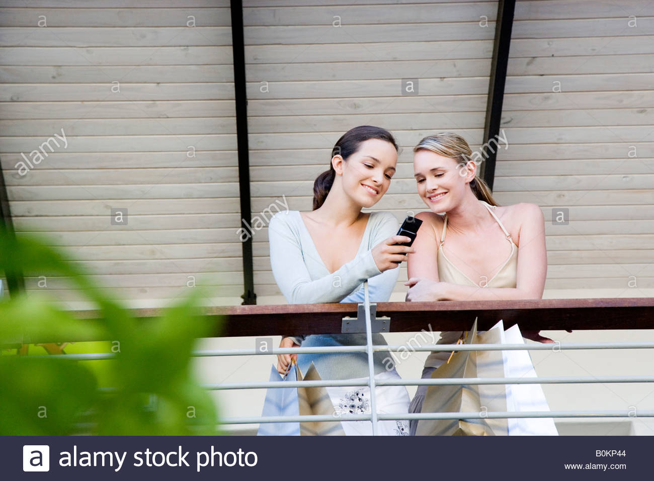 Two women on a balcony looking at a mobile phone - Stock Image