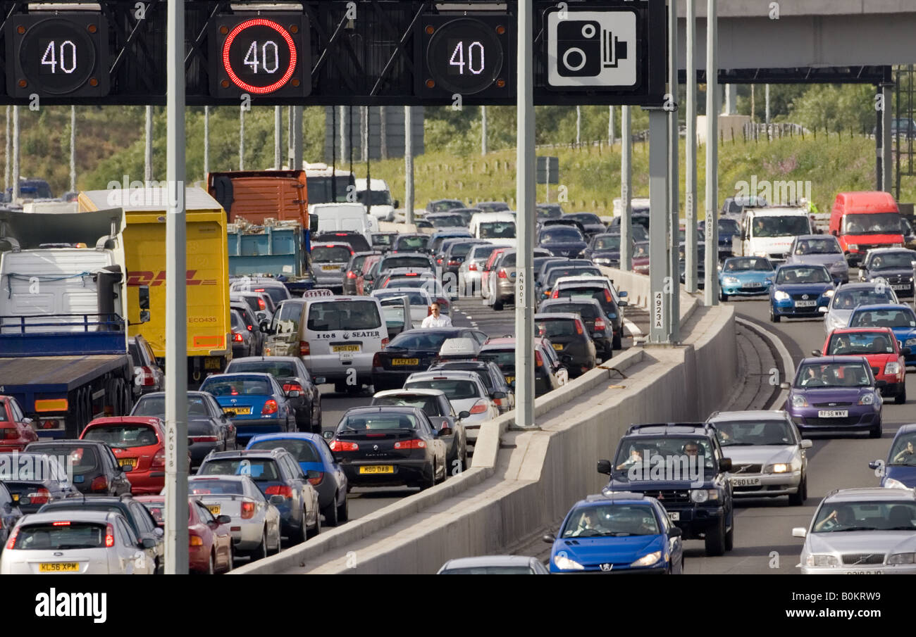 Man inspects vehicle damage after accident in traffic congestion on M25 motorway near London United Kingdom - Stock Image