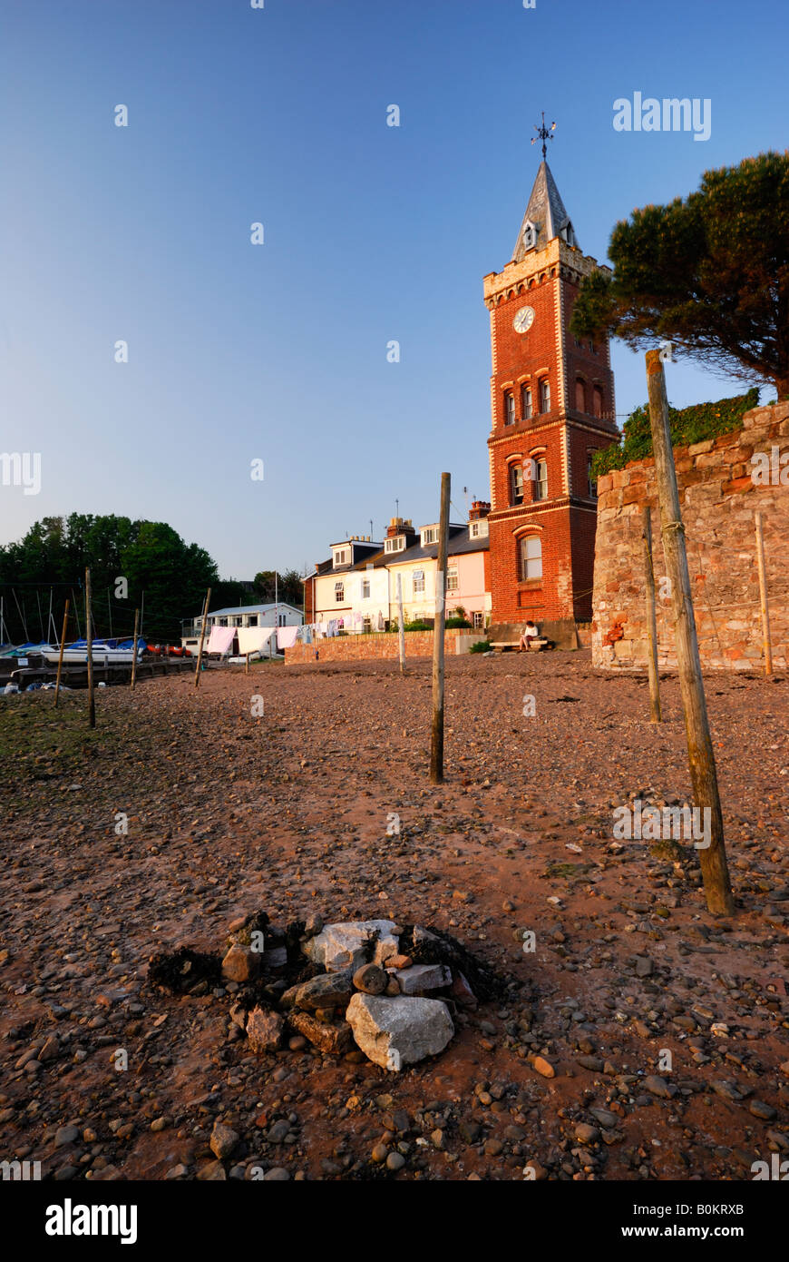 View of clock tower at Lympstone, Devon, UK from the Exe Estuary at low tide in evening light - Stock Image