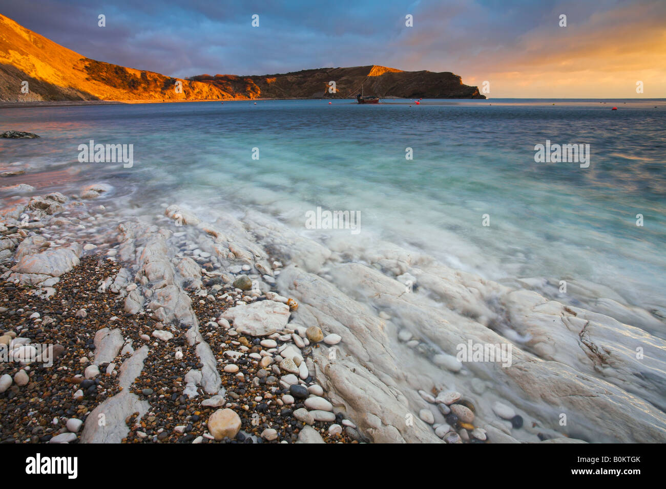 Sunlight glows on the cliffs at Lulworth Cove in Dorset England - Stock Image