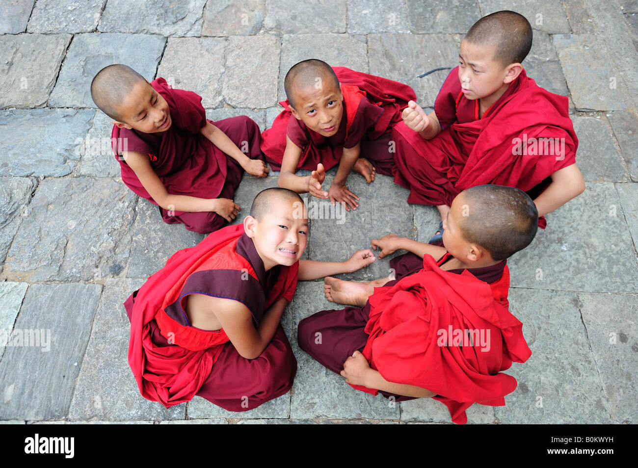 Young Bhutanese Buddhist monks resting from studies at the Wangdue Phodrang Monastry Dzong  in central Bhutan. Stock Photo