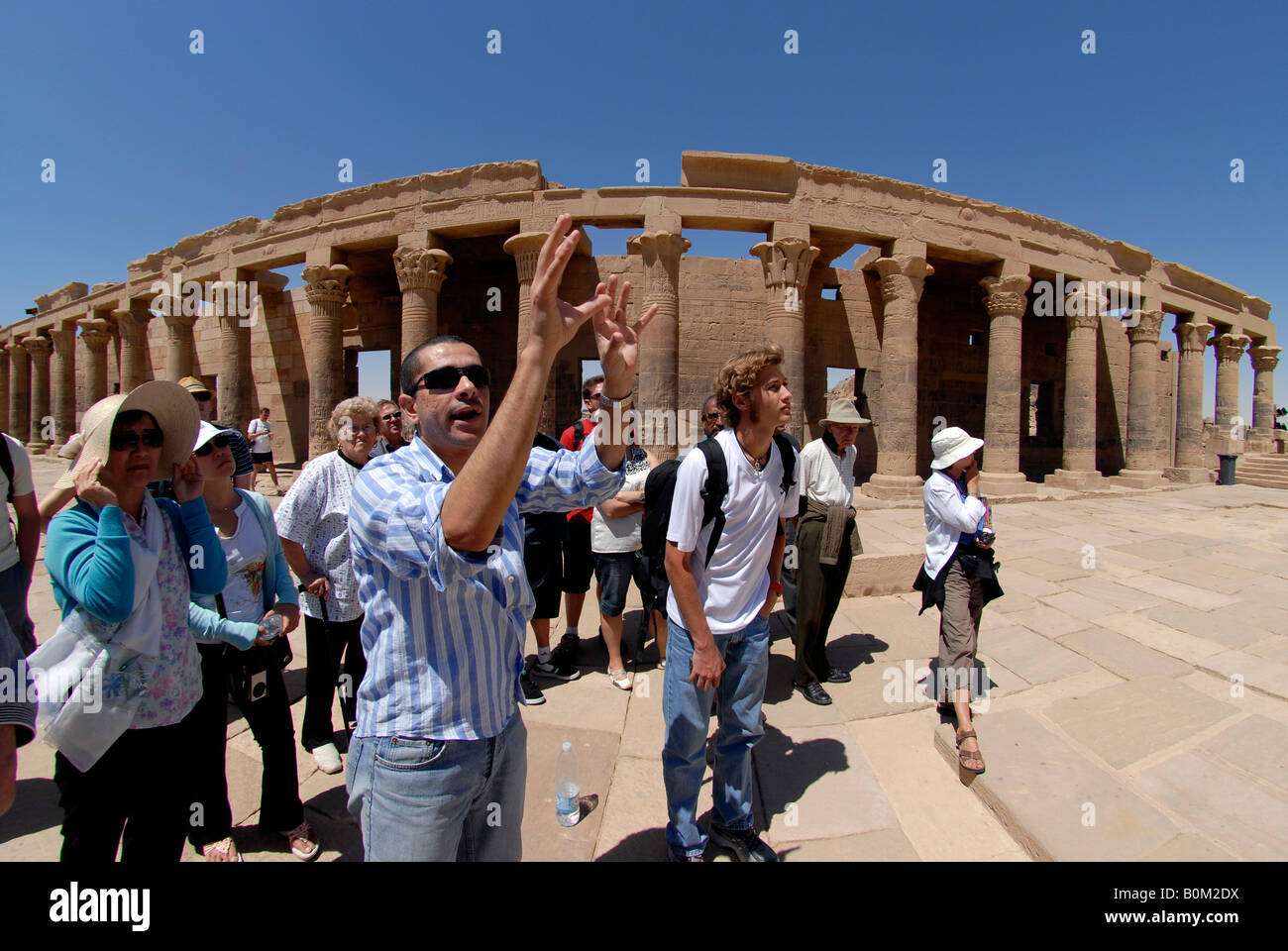 An egyptian tour guide with tourists by the colonnade at the.