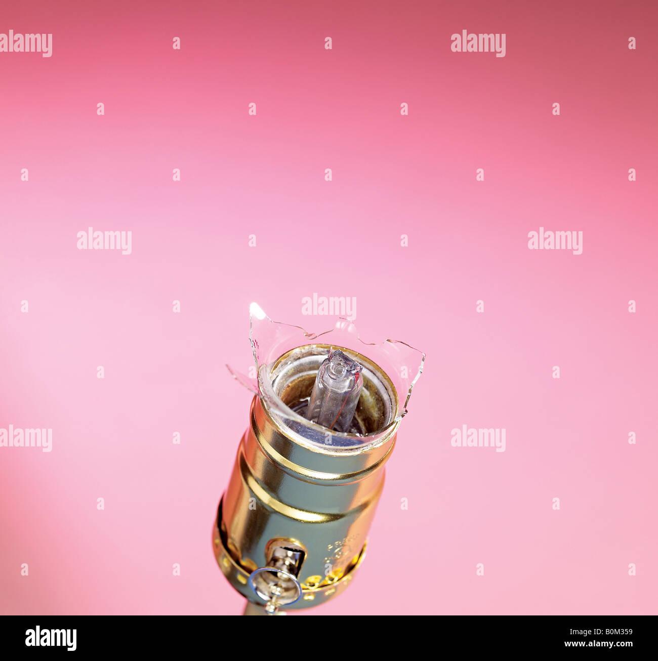 Broken Lightbulb in the socket against pink background - Stock Image