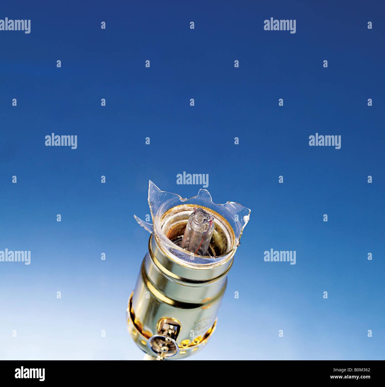 Broken Lightbulb in the socket against blue background - Stock Image