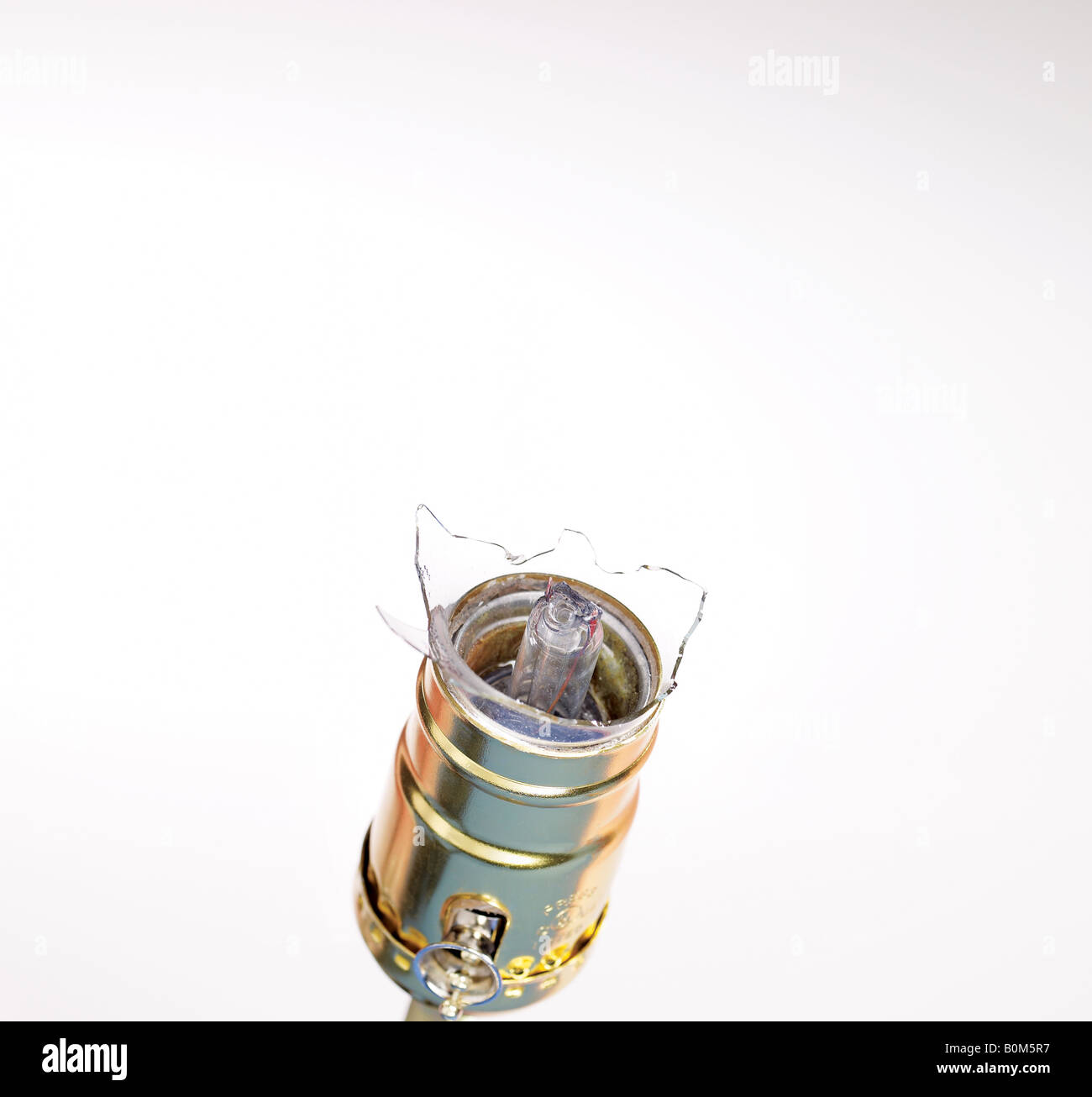 Broken lightbulb in the socket against white background - Stock Image