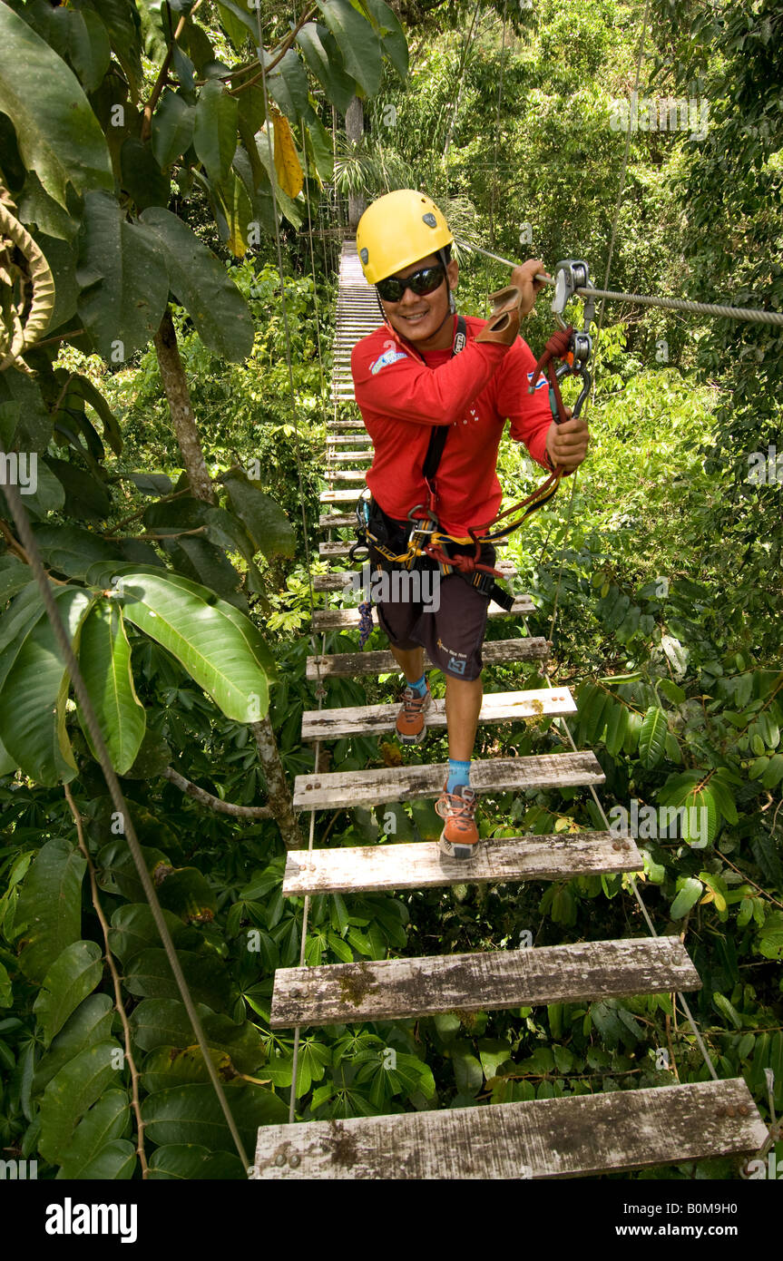 COSTA RICA Man crossing suspension bridge over jungle canopy on zip line canopy tour. Pacuare River Lodge. Caribbean - Stock Image