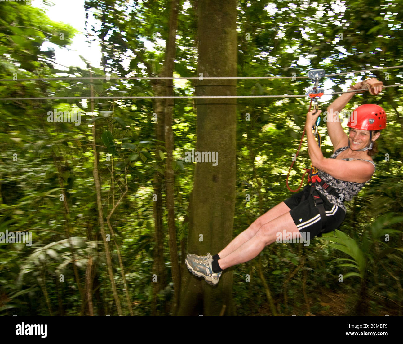 COSTA RICA Smiling Mature woman taking off on a zip line canopy tour. Pacuare River Lodge. Caribbean Slope - Stock Image